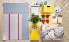 Imagem com uma caixa de cartão amarela, um candeeiro de secretária, quadros em rosa e cinzento, um relógio amarelo, conjunto de capa para edredão e fronhas em cinzento/amarelo/laranja, canecas castanhas e uma caixa de arrumação branca, da IKEA.