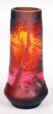 Émile GALLÉ (1846-1904)  Émile GALLÉ (1846-1904)  VASE en verre triple couche rouge rubis et orange sur fond jaune à décor dégagé à l'acide de paysage lacustre. Signé. (Fêle). H.: 15,5 cm