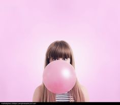 Caucasian woman blowing large bubble gum bubble - stock photo