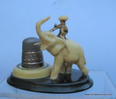 Bakelite thimble holder, a novelty in the form of a man riding on an elephant. English cir 1940. Silver thimble on stand included.