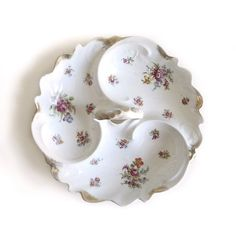 This is a very exquisite three compartment serving centerpiece made of porcelain.  This serving dish consists of three compartments with golden scalloped edgings. This large three compartment service dish with its center handle is decorated with very exquisite flowers or blossoms and an embossed center handle.   #dishes#tableware#service, kitchenware,plate,cup,glass,porcelain