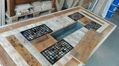 Tafel gemaakt van oude kaasplanken en oude pallets en steigerhout.  En 4 vakjes ingelegd met bierflesdopjes en afgegoten met een doorzichtige epoxy. En het midden zit een deksel en als je die eraf haalt zit er een bakje.