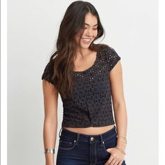 American eagle eyelet twisted shirt I bought this shirt two months ago. I never wore it because it was too big so I decided to sell it on here. I bought it for 35 USD but I'm selling it for 26. The shirt is see through so you would need to wear something underneath. It's a dark grey American Eagle Outfitters Tops Crop Tops