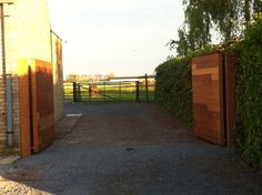 Handmatige opritpoort op maat in afzelia hout wordt geopend op zijn plaats gehouden door handige kliksystemen #gate #garden #wood www.emts.be