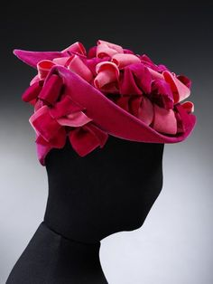 Hats were considered an essential fashion accessory in the 1950s. The two main styles during this time were small skull-caps, or wide saucer hats. A hat such as this would be suitable for a cocktail party or dinner.  This hat was designed by the Danish-born Aage Thaarup (1906–1987), who moved to London in the 1930s. Thaarup was one of the most successful milliners of his age, and also designed for the Queen.