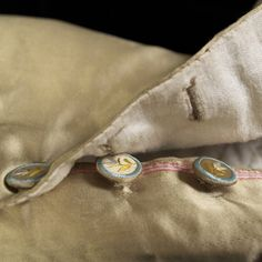 Detail of buttons on breeches. When the buttons at the knee of the breeches are unbuttoned, the pink selvedge edge of the satin is visible. The inclusion of the selvedge indicates that the tailor used the entire width of fabric. It also makes the edge easier to finish since the selvedge will not unravel. | KSUM 1983.1.22 a-c