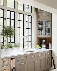 Taupe beige cabinets in kitchen with wood accents and black steel windows.