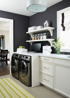 Laundry/mudroom - Navy walls, lime green rug, white cabinetry, open shelving, built-in washer/dryer units… What's not to love?