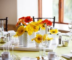 Colorful, fresh gerbera daisies are placed atop a rectangular platform, creating a visually dynamic centerpiece.