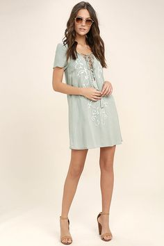 Fall in love to the rhythm of a steel drum band in the Down in Kokomo Dusty Sage Embroidered Shift Dress! This vacation-ready number is made from lightweight rayon with short sleeves and a lace-up neckline. Ivory embroidery decorates the shift bodice.