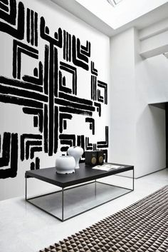 Black and white geometric art on the wall. Rug with black and white triangle pattern