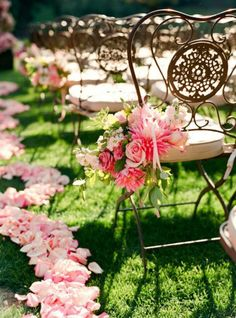 Floral clusters on chairs and petals lining the isle.