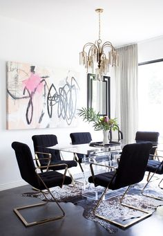 Black and white dining space with graffiti artwork, crystal chandelier, and flowers in vase