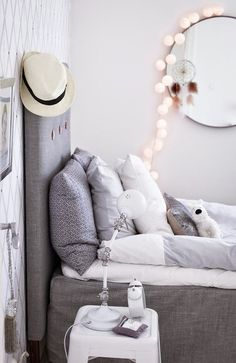 Grey bedroom. Details: Dreamcatcher, lights, Buttons on the headboard | @andwhatelse