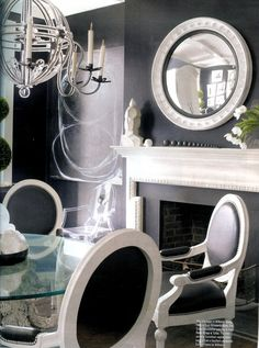 Dining room by Mimi Williams. She can do pale neutral rooms and here's her black. Love the ghost chair to left of mantle paired with the abstract art above. Look at the simplicity and balance of the objects on the mantle.