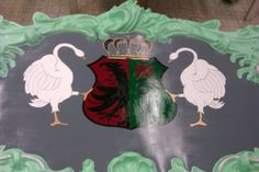 In this picture the whole shield, including the swans and the crown, is finished. The crown is gold with dark grey and we also applied some shadow. We did this using darker and lighter grey than the grey we first used.