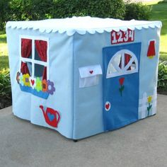 Playhouse made from fabric draped over a card table.