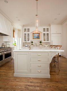 white kitchen  ~ putty coloured island ~wood  floors ~marble counters