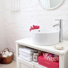 Paint a junk-shop low-level cupboard with white eggshell and conceal the plumbing for a countertop basin inside, drilling holes for the tap and waste pipe.