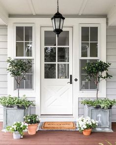 Farmhouse style front door styling for major curb appeal. Farmhouse style front door styling for major curb appeal. Image Size: 500 x 618 Source Front Porch Plants, Front Porch Design, Galvanized Planters, White Planters, Porch Planter, Modern Farmhouse, Farmhouse Style, Farmhouse Decor, White Farmhouse