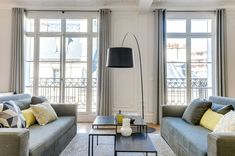The living room, which is the result of joining two rooms together, has large windows and traditional French balconies. Period details and plasterwork have been restored with great care.   See more --> http://magazine.designbest.com/en/projects/period-apartment-with-unique-Parisian-flair/?utm_source=pinterest&utm_campaign=SOCIAL-activities&utm_content=period-apartment-with-unique-Parisian-flair%2F