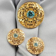 14kt Gold and Blue Zircon Suite, comprising a brooch and earrings each centering a circular-cut blue zircon, pierced mounts, 12.6 dwt, dia. 1 1/4, 7/8 in., the earrings signed Shreve, Crump & Low.