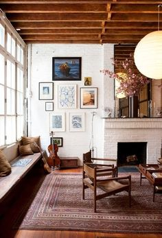 I love the painted brick, exposed beams, and warm rug.