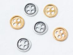 Botón de zamak bañado: en plata y dorado.