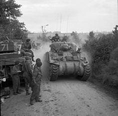 Sherman tanks of 33rd Armoured Brigade, supporting 3rd Infantry Division, moving forward near Lebisey Wood for Operation CHARNWOOD, the assault on Caen, 8 July 1944.