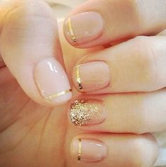 A nude manicure with gold accent lines and glitter for a glam bride on her wedding day.