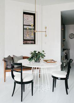 Decoração com preto e branco . O banco de madeira com almofadas e a planta deram um toque  moderno e jovial ao ambiente .