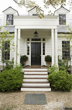 White siding; dark door; large windows; love entry way and steps: wood flooring, deep and covered; like the gravel.