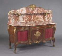 A Fine Louis XVI Style Gilt-Bronze Mounted Buffet À Gradin, With A Rouge des Flandres Marble Top and Back Panel France, Circa 1890 A Fine Louis XVI Style Gilt-Bronze Mounted Buffet À Gradin, With A Rouge des Flandres Marble Top and Back Panel. The bronze mounts stamped to the reverse 'ROGIE'. This imposing buffet has a Rouge des Flandres marble superstructure above a corresponding shaped marble top. The marble back panel with a shelf and surmounted by a fine gilt-bronze mask. Below are three…