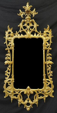 "A George III Giltwood Pier Mirror, CIRCA 1765, Height: 63 1/2"" Width: 29 ½"". The shaped rectangular plate set within stylized architectural elements issuing finely carved pierced foliate and floral swags, centered by acanthus carved cresting; with conforming C-scroll decoration throughout."