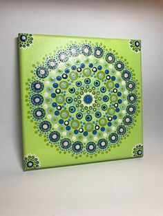 "Original Mandala Painting on Canvas, Dotilism, Dot Painting, Aboriginal Art, Henna Meditation Art, Healing/ Calming, Hand Painted with acrylic paint on Canvas , sprayed multiple times with high gloss sealer to protect paint and aging. Colors are: green, blues, yellows Canvas size: 8"" x"