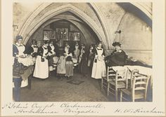 Photograph showing nurses of the St. John's Ambulance Brigade distributing clothing to poor children in the Crypt of the Priory Church of the Knights of St. John, Clerkenwell, London, by Henry Walter Fincham, 190