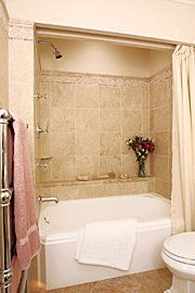 Trim molding & shelf. In a small bath, fixtures take on great prominence. A cast-iron tub with faceted corners surrounded by tumbled marble tile distinguishes this bath.