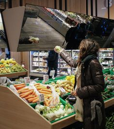 Above the produce, there are long reflective screens.