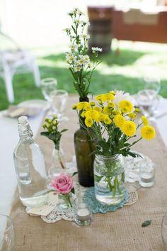 Summer-Garden-. Algo muy de moda es poner un centro de mesa natural conformado de frascos, botellas y carpetitas, sin olvidar hermosas flores naturales.