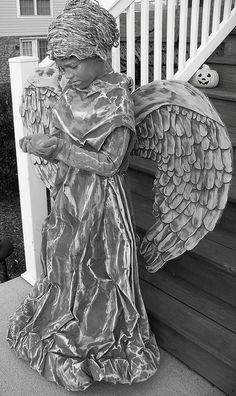 handmade Weeping Angel costume  The dress is an old sheet that I painted with medium gray, country gray, & white. I stuffed old catalog pages in the bottom for ruffles. I made the wings from foam core board & the feathers from craft foam. The wig is gray yarn glued to a shower cap (also painted) & yes, I painted her hands & face to match.