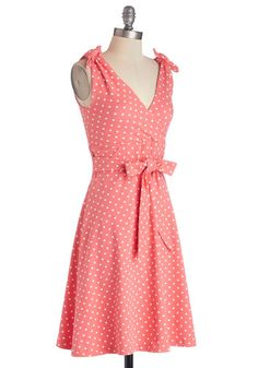 Take in the brilliant sun, lush scenery, and local sights as you celebrate another whirlwind year wearing this sweet, polka-dotted dress! With a self-tie sash that matches the knotted bows atop each shoulder strap, this coral-pink frock infuses a day of fun with bright, casual style. Complement the surplice neckline of this effortlessly classic piece with espadrille wedges, mint sunnies, and a sprawling straw hat, then present yourself to your friends for the next surprise!
