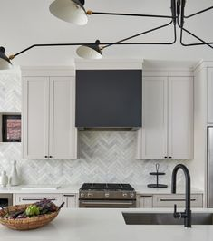 Black dome kitchen range hood between light gray shaker cabinets boasts thin marble herringbone tiles in a transitional kitchen. Shaker Kitchen Cabinets, White Shaker Cabinets, Black Cabinets, Modern Shaker Kitchen, Kitchen Black, Kitchen Cupboard, Modern Kitchens, Kitchen Redo, Kitchen Designs