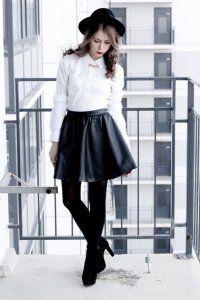 Классическая женская рубашка средней длины белого цвета в сочетании с короткой юбкой чёрного тона, шляпой чёрной расцветки и замшевыми чёрными сапогами на высоком каблуке.