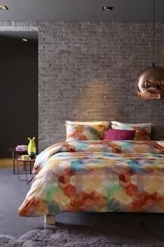 Exposed brick wall, and a touch of plum, hexagons, and Tom Dixon's copper pendant.