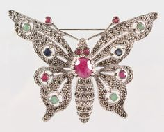 A SILVER, RUBY, EMERALD, SAPPHIRE AND MARCASITE BUTTERFLY BROOCH.