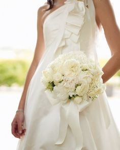Tied with a satin ribbon that echoes the detailing on the bride's gown, this all-white bouquet includes peonies and late-season garden roses for a timeless look.