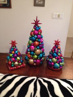 "DIY ornament Christmas trees, copied from boring store versions.  I make cones from poster board using cardboard cones for shape. Use graduated sized ornaments, and 1/4 to 1"" balls to fill the gaps as well as 1/2"" glitter ribbon. Top with star ornament. Very popular gifts."