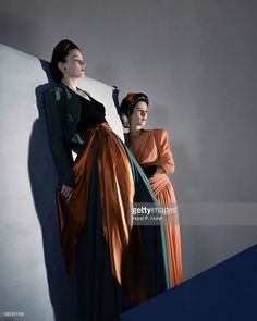 Two models, one wearing orange, green, and black silk gown, the other, Barbara Cushing, later known as <a gi-track='captionPersonalityLinkClicked' href=/galleries/search?phrase=Babe+Paley&family=editorial&specificpeople=968974 ng-click='$event.stopPropagation()'>Babe Paley</a>, wearing an orange gown with a sash
