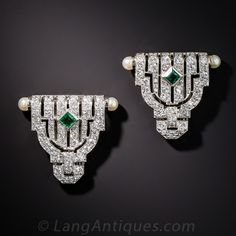 Measuring just shy of one inch in both directions, this relatively petite pair of original Art Deco dress clips are perfect for both dressy or semi-dressy occasions. They were expertly hand-fabricated in platinum during the zenith of the Art Deco design period  (circa 1925), and sparkle with an array of small bright white diamonds, a pair of square emeralds, and lustrous pearl terminals. An artful use of negative space  produces a striking geometric design. Little gems.