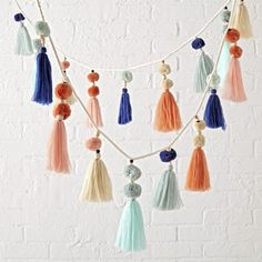 Shop Pastel Tassel Garland. This colorful hanging garland is like a party for your décor. It's adorned with playful tassels, pom poms and wooden beads for a truly festive look.